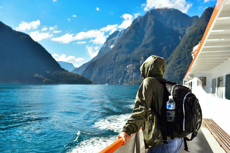 Man in a jacket holding a backpack with a bottle of water, standing on a boat deck and travelling along Milford Sound fiord in New Zealand. 版權商用圖片