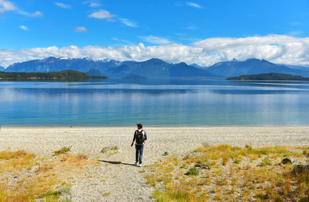 Blue clean waters of Manapouri lake with the view of Fiorland mountains in New Zealand. A man with a backpack runs to the lake. 版權商用圖片