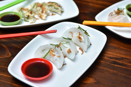 Traditional asian rice dough steamed dumplings with stuffing, spring onion and fried chips decor, served with spicy chilly sauces 版權商用圖片