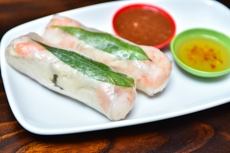 Traditional Vietnamese cuisine dish - fresh spring rolls wrapped in transparent rice paper with prawns, vermicelli, mint and carrots inside served with spicy sauces 版權商用圖片
