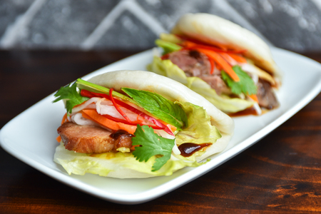 Fresh delicious pork steamed buns with BBQ sauce, coriander, mint, salad leaf and vegetalbles carrots, capsicum