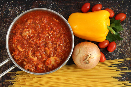 Bolognese sauce in pot with dry pasta and vegetables Stock Photo