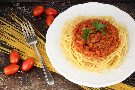 Spaghetti bolognese on white plate with dry pasta Stock Photo