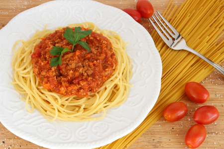 Spaghetti bolognese on white plate with dry pasta photo