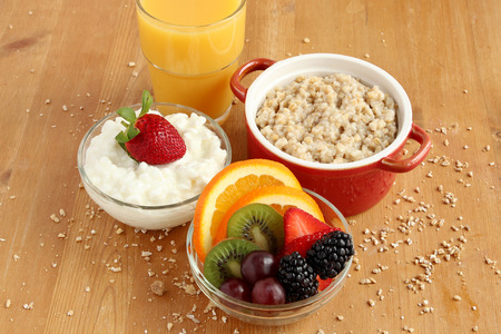 Healthy breakfast of fruit, cottage cheese, oatmeal and orange juice photo