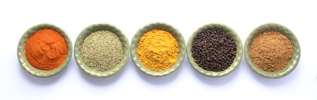 Spices -  paprika, rosemary, curry, black pepper, cumin - in green bowls