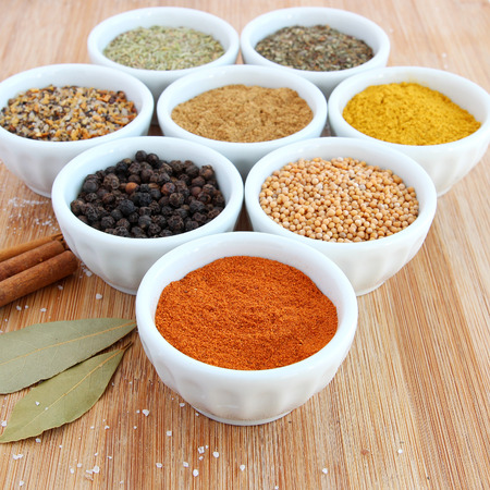 Spices in white bowls – Paprika in the foreground 스톡 콘텐츠