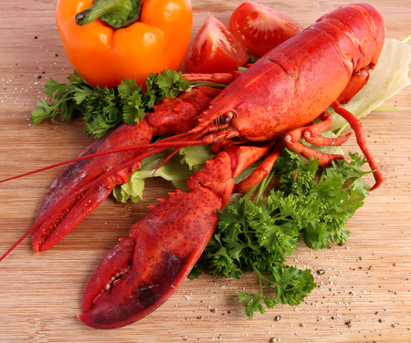 Cooked lobster with various vegetables on wooden board photo