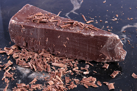 Big chunk of milk chocolate and shavings on black marble background Stock Photo