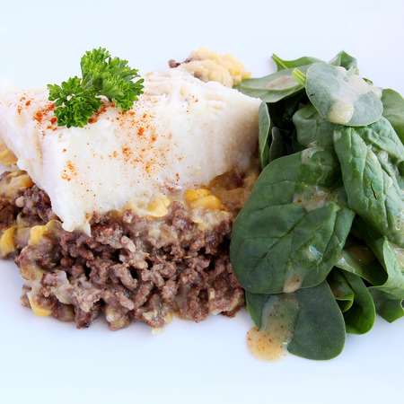Shepherd s pie and spinach salad in white plate photo