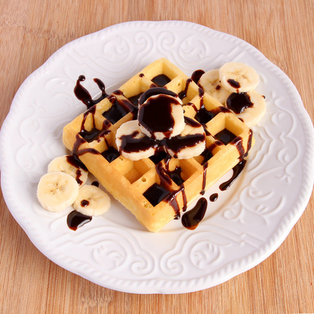 Banana-chocolate waffle in white plate on wooden board