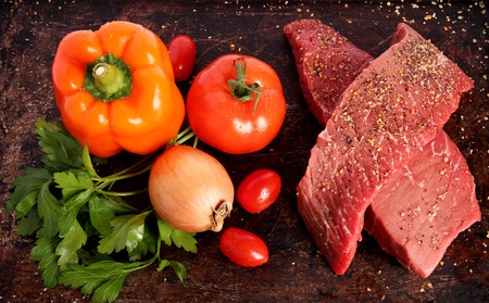 Two raw steaks with vegetables and spices on brown  Stock Photo