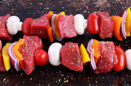 Uncooked beef kebabs with vegetables and spices on brown