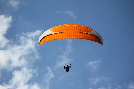 An orange paragliding in a blue sky