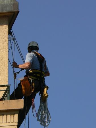 andamio: hombre suspendido y cielo azul Foto de archivo