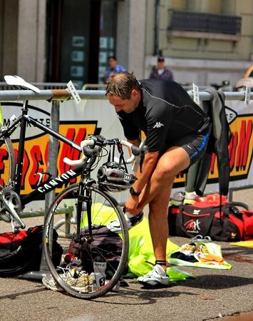 swimm: GENEVA, SWITZERLAND - JULY 24 : one unidentified male racing cyclist after the swimm race at the international Geneva Triathlon, on july 24, 2011 in Geneva, Switzerland