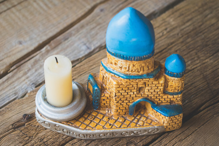 Candlestick in the Uzbek style in the form of a minaret. On a wooden background with a candle.