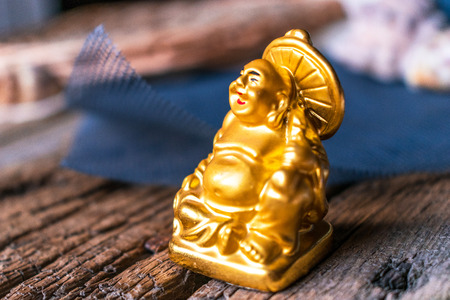 Deity Hotei is a statuette. Talisman for good luck and health. Laughing little man is a golden figure.