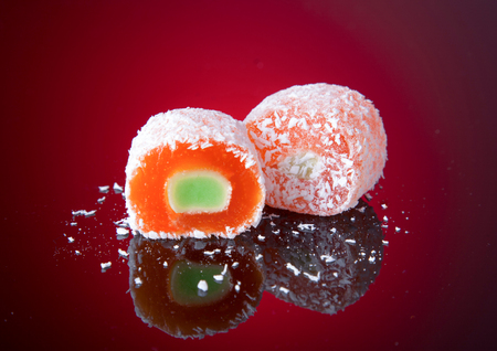 Marmalade sweets with filling and powdered sugar on a red background. Gelatin or marmalade candy.