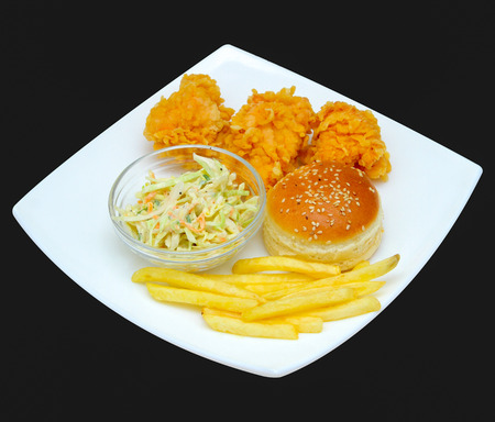 Chicken nuggets with french fries, greens on a plate. On a dark background.