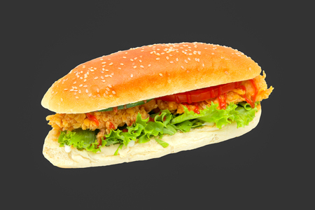 Hamburger with chicken nuggets, herbs, tomatoes in a bun. On a dark background.