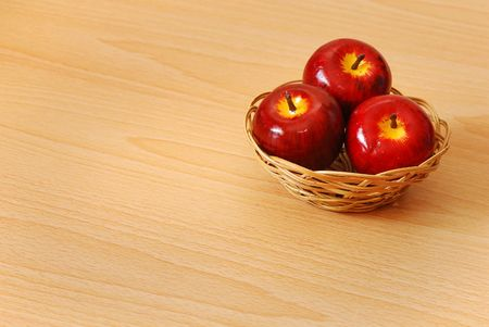 Three red apples in a basket