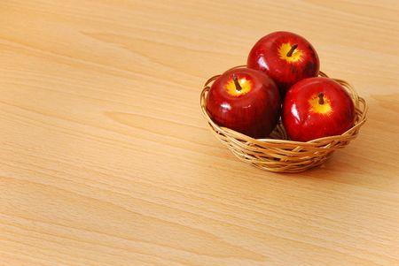 Trois pommes rouges dans un panier