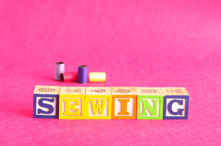 spelled: The word sewing spelled with colorful alphabet blocks displayed with spools of thread against a pink background Stock Photo
