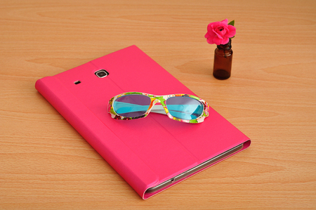 portability: A tablet computer in a pink case on a table with a pink rose in a brown bottle and a pair of colorful sunglasses