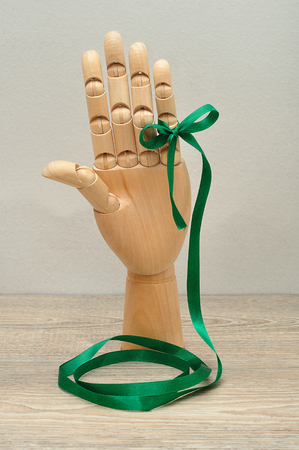 finger bow: A mannequin hand holding a green ribbon that is tied to one finger with a bow isolated against a white background Stock Photo