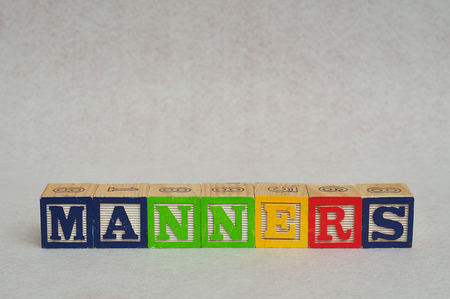 spelled: The word manners spelled with colorful alphabet blocks isolated on white background