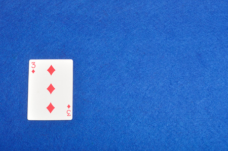 diamonds isolated: Playing card. Three of diamonds isolated on a blue background