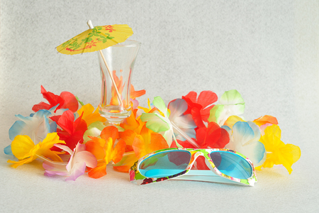cocktail umbrella: A colorful flower garland displayed with a cocktail umbrella and sunglasses on a white background