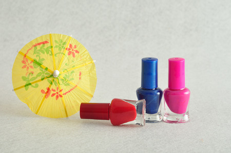 cocktail umbrella: Colorful nail polish displayed with a cocktail umbrella on a white background