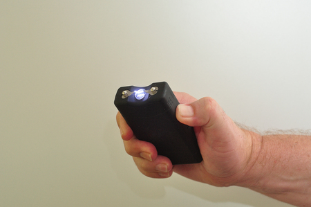 electroshock: A taser held in a mans hand isolated on a white background