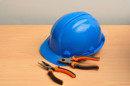 long nose: A blue hard hat displayed with a set of pliers and a long nose pliers