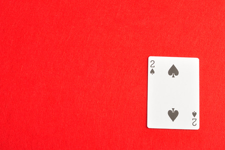 spades: Playing card. Two of spades isolated on a red background