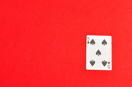 spades: Playing card. Five of spades isolated on a red background