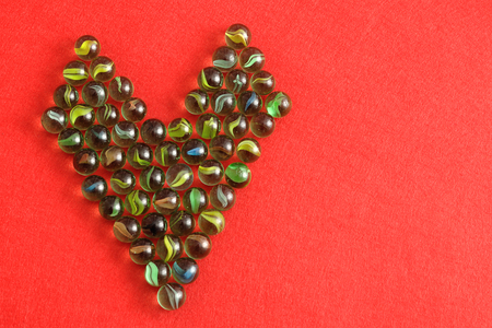 group of colourful ball: Marbles displayed in a heart shape on red background Stock Photo