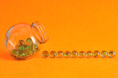 big ball: A collection of marbles in a glass jar displayed on an orange background Stock Photo
