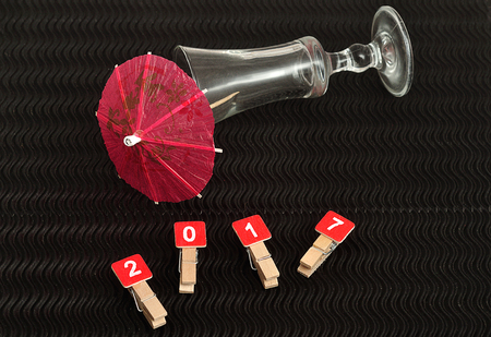 cocktail umbrella: 2017 spelled with red blocks displayed with a shooter glass with a red cocktail umbrella on a black background Stock Photo