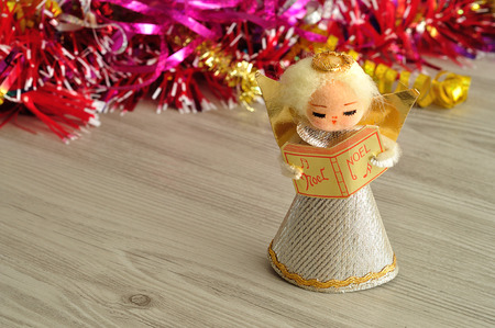An angel to decorate a Christmas tree with tinsel in the background