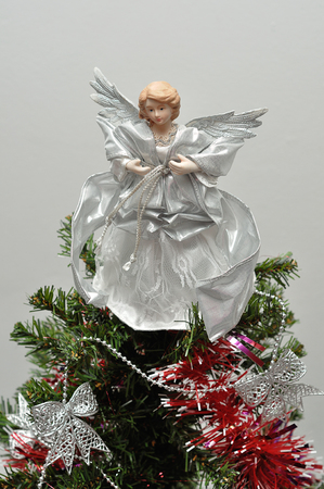 topper: An angel tree topper on top of a Christmas tree