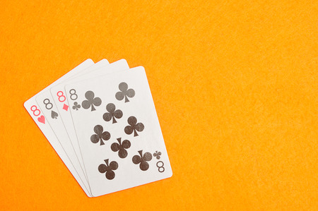 The different suit of the number 8 cards in a deck of cards displayed on an orange background