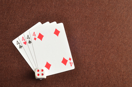 4 of a kind: The different suit of the number 4 cards in a deck of cards displayed on a brown background with a dice