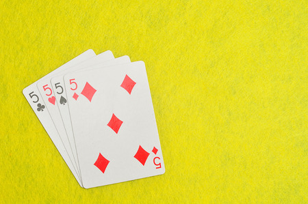 The different suit of the number 5 cards in a deck of cards displayed on a yellow background Stock Photo