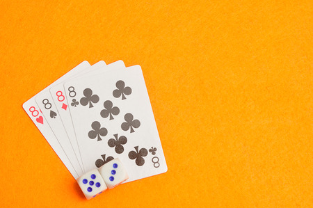 The different suit of the number 8 cards in a deck of cards displayed on an orange background displayed with two dices
