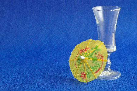 cocktail umbrella: A yellow cocktail umbrella displayed with an empty shooter glass isolated on a blue background