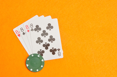 The different suit of the number 8 cards in a deck of cards displayed on an orange background displayed with a green poker chip Stock Photo