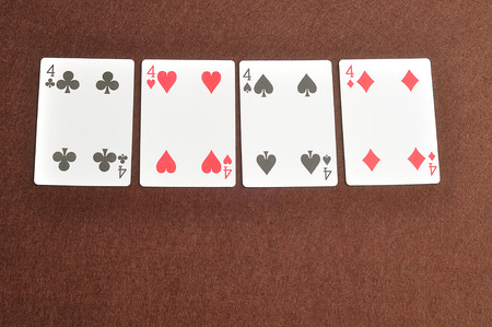 four of a kind: The different suit of the number 4 cards in a deck of cards displayed on a brown background